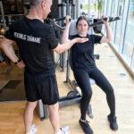 Personlig-tränare-med-adept-på-gym-i-maskin